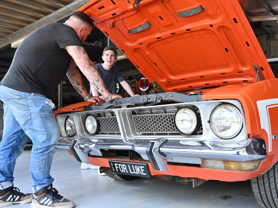 Ben and his son, Luke, working on a car together. The car is displaying Ben's F O R L U K E personalised plates.