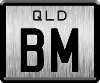 Framed ID plate with black writing on a brushed metal background. The combination reads B M.