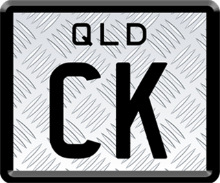 Framed ID plate with black writing on a checkerplate background. The combination reads C K.