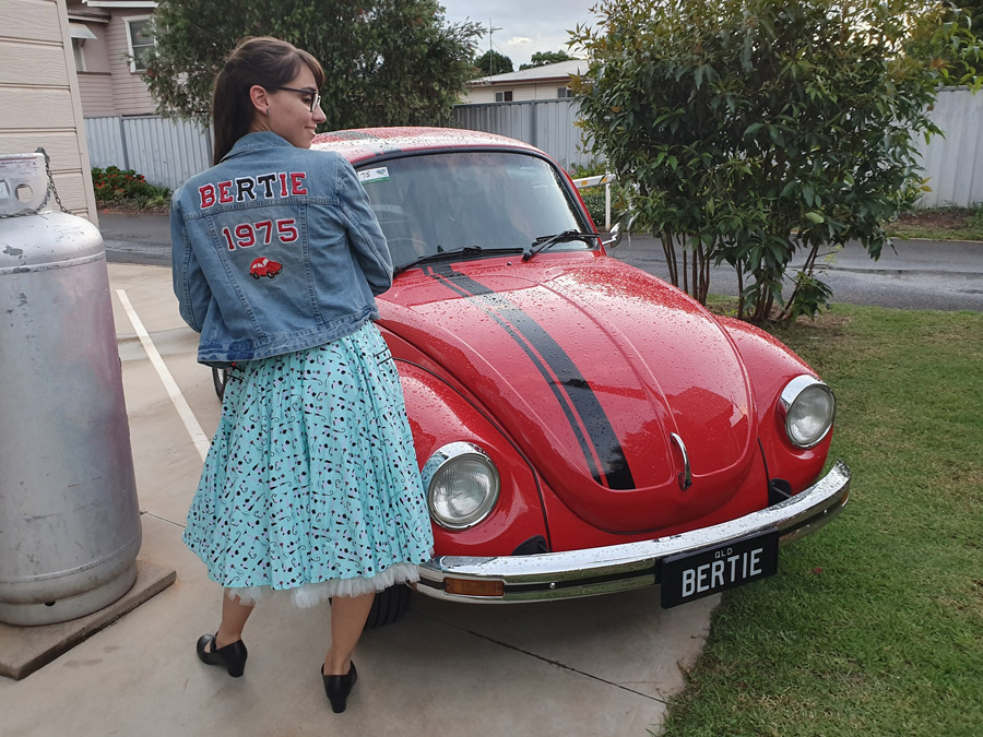 Kirrily posing next to Bertie, showing off her customised denim jacket with the word 'Bertie' in large letters across the back.
